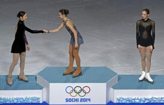 First-placed Russia's Adelina Sotnikova (C) shakes hands with second-placed South Korea's Kim Yuna (L) as third-placed Italy's Carolina Kostner looks on, on the podium after the figure skating women's free skating program.